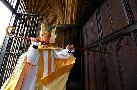 The Archbishop bangs on the door of Canterbury Cathedral three times.